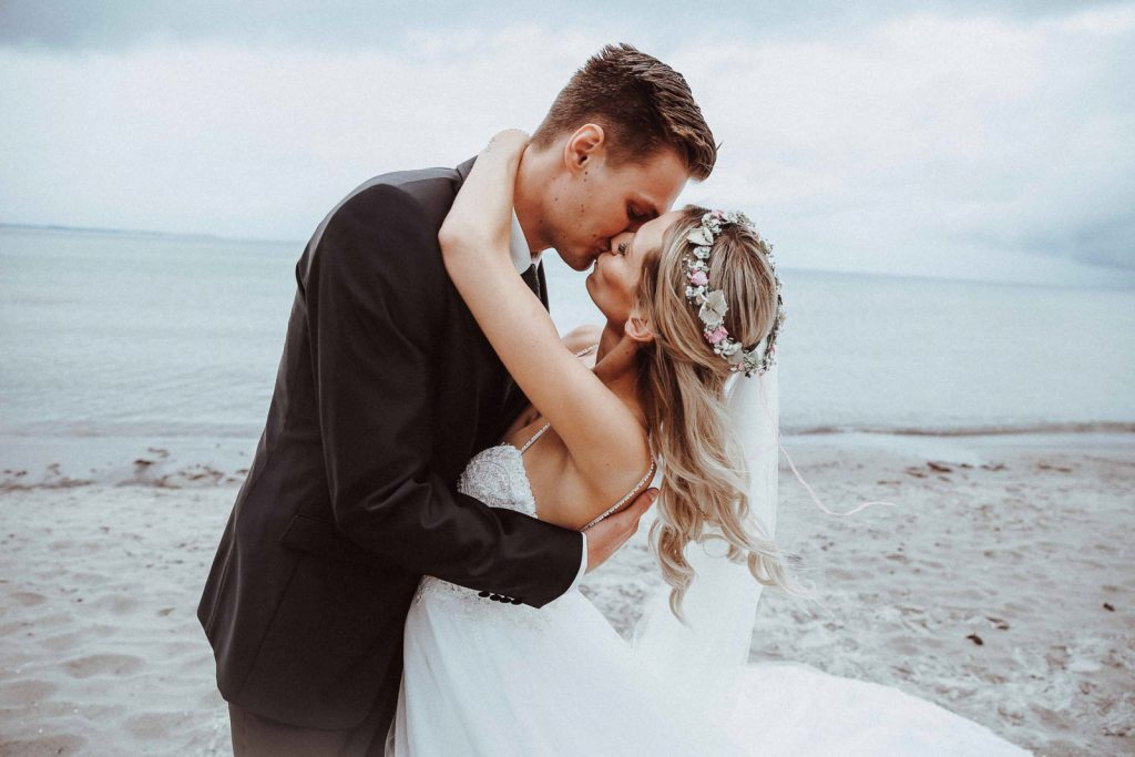 Los Angeles Wedding photographer pricing - Bride kissing on a beach in Los Angeles